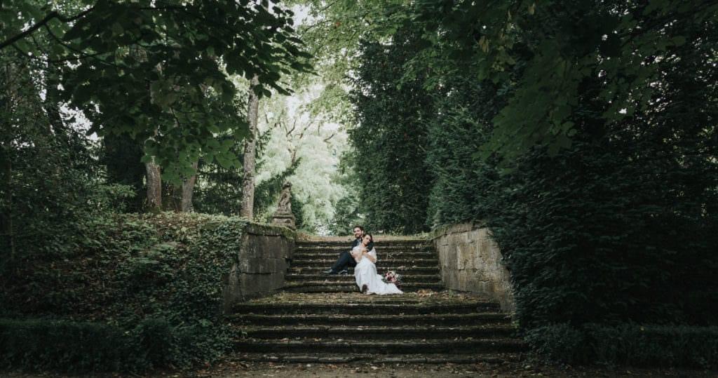 mariés assis sur les marches dans le jardin du chateau de boucq