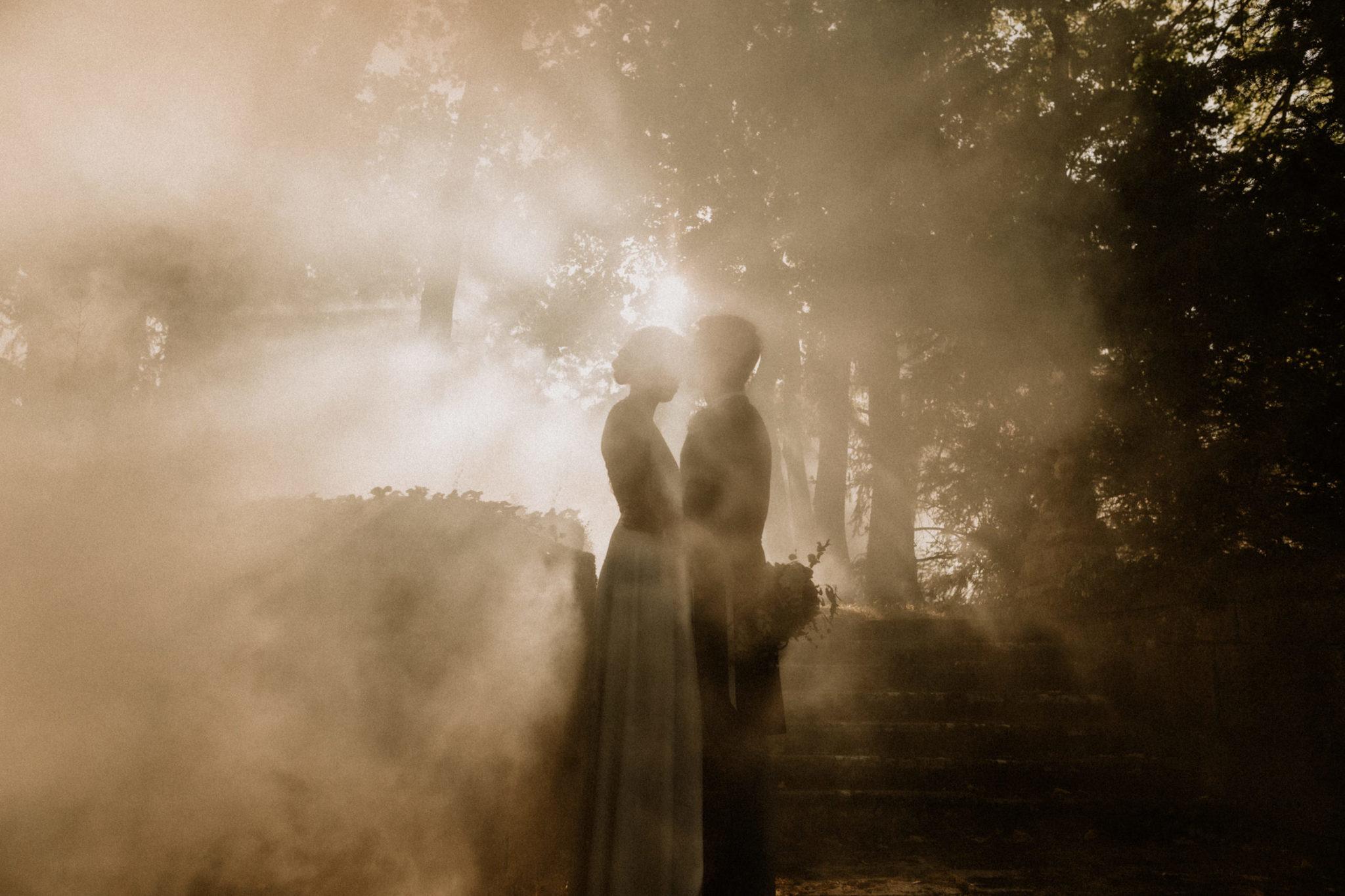 couple de mariés qui s'enlacent dans la brume au chateau de boucq