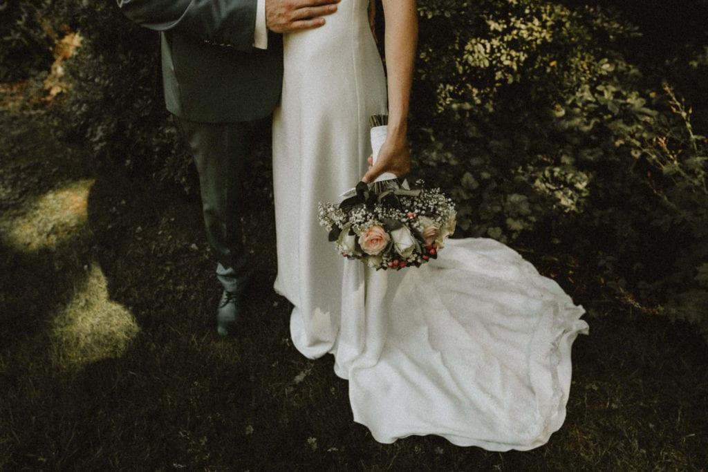 gros plan sur le bas d'une robe de mariée avec un bouquet