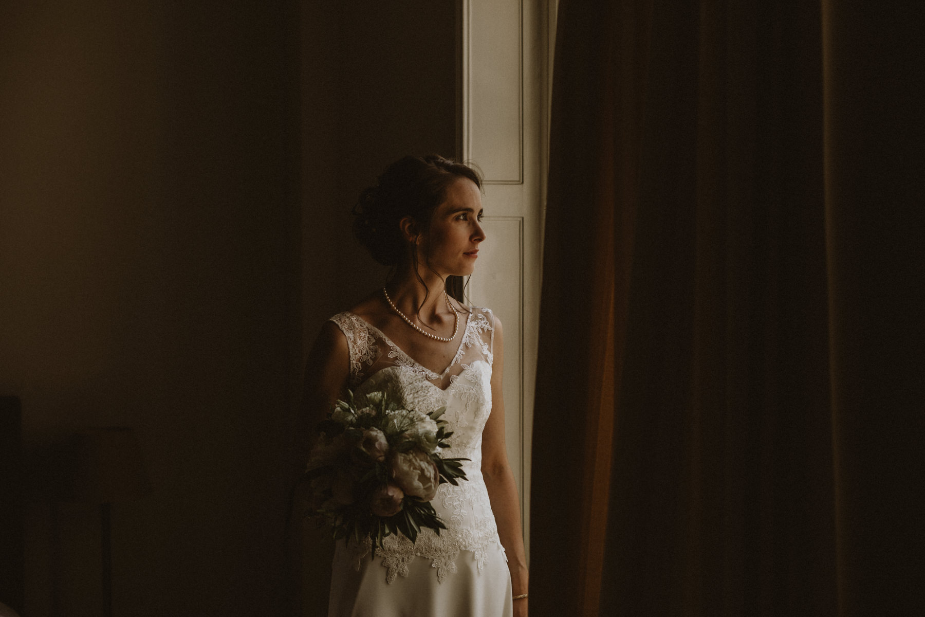 mariée qui regarde par le fenêtre avec son bouquet à la main à la maison de myon
